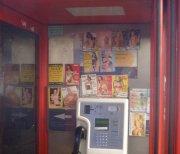 Eine Vielzahl von Werbeaufklebern von Prostituierten in einer roten Londoner Telefonzellen